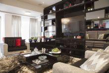 Sala de estar e Tv com estante preta.